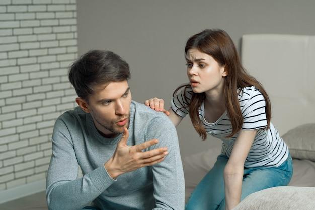 男と女がベッドに座って、関係、本当の口論について話している