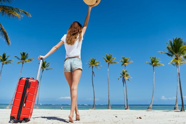 若い美しい女性は赤いスーツケースで背中を立っています。