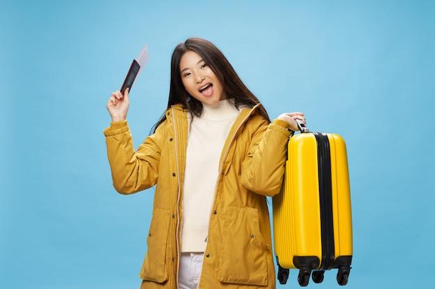 アジアの女性は彼女の手でスーツケースと一緒に旅行します