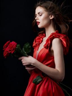 赤いドレスを着た彼女の手に赤いバラを持つ若い女性