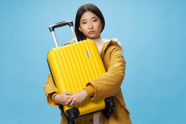 アジアの女性は彼女の手で休暇をスーツケースで旅行します。