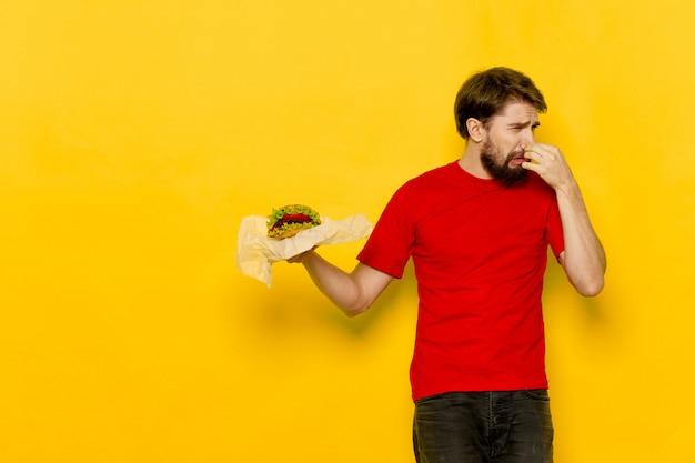 彼の手でジューシーなハンバーガー、ハンバーガーを食べる男と若い男