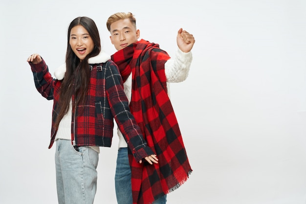 アジアの女性と一緒にモデルをポーズ明るい色の背景上の男