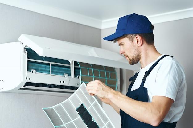 男の修理およびクリーニングエアコン、自宅の労働者