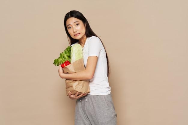 Азиатская женщина с бумажной сумкой овощей