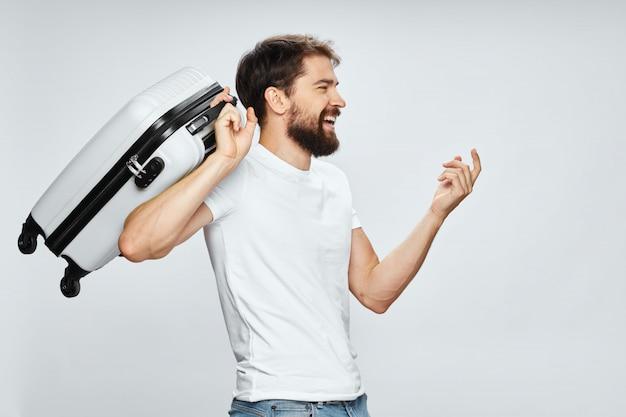 彼の手のポーズ、休暇でスーツケースを持つ男性旅行者