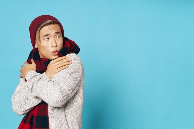 Азиатский мужчина в теплой зимней одежде позирует