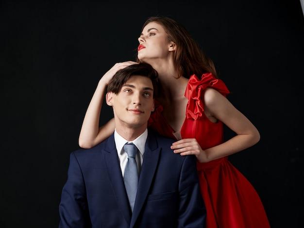 男と美しいドレスを着た女性は、休日のカップル、セクシーなカップルの美しい肖像画を抱擁します。