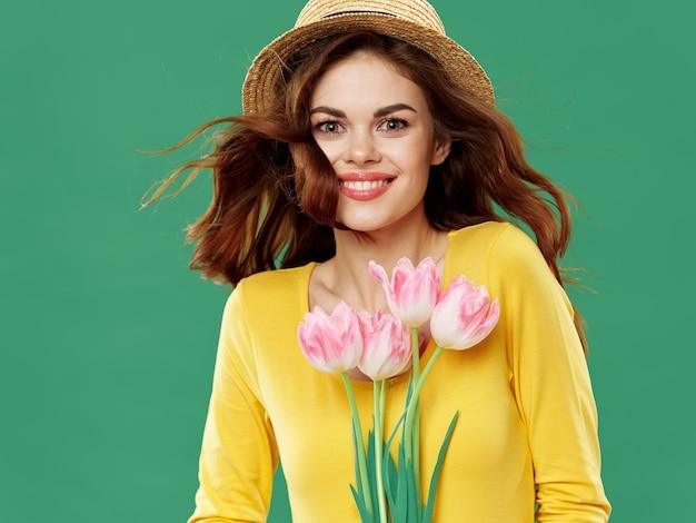 Весной молодая красивая девушка с цветами на цветной студии, женщина позирует с букетом цветов, женский день