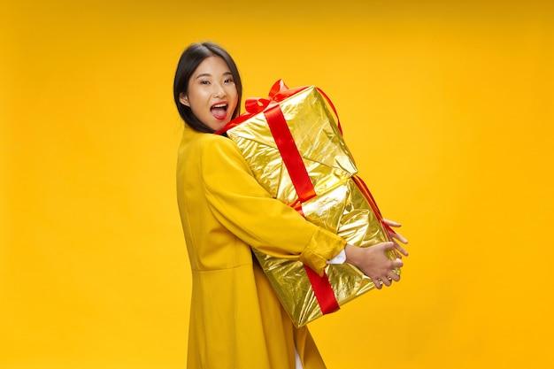 誕生日やクリスマスの巨大なギフトボックスを持つアジアの女性