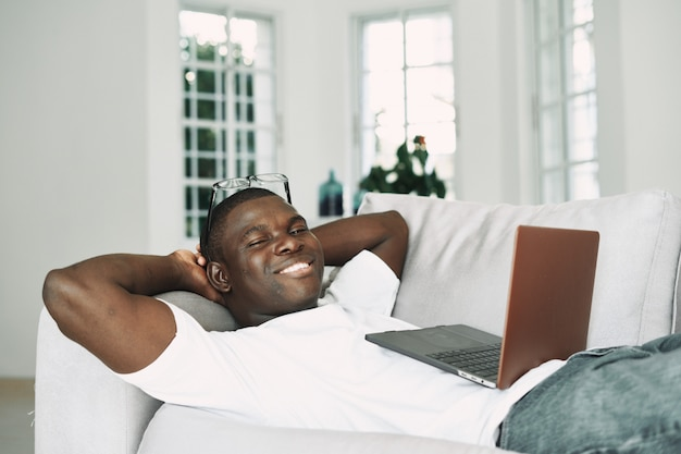自宅で仕事をしているアフリカ系アメリカ人のフリーランサーのラップトップ