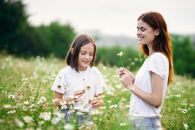 野の花を摘んで花を持つフィールドの女性と子供の女の子