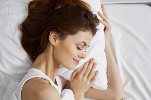彼女の美しい白雪姫のベッドで美しい若い女性がリラックスします。