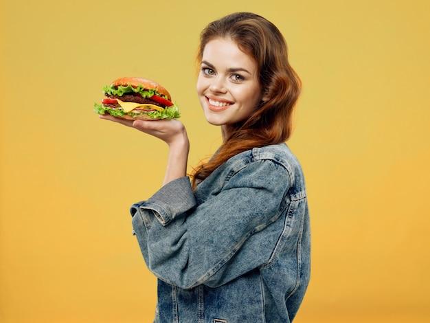 彼女の手でジューシーなハンバーガー、ハンバーガーを食べる女性と美しい若い女性