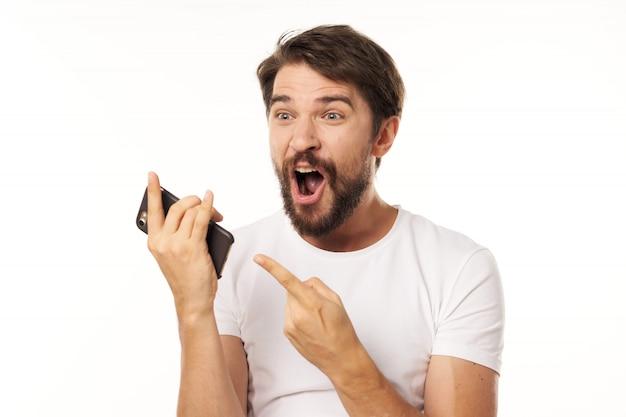 驚いたと彼女のスマートフォンを指しているハンサムな男性モデル