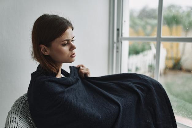 ウィンドウで自宅の肘掛け椅子で休む若い女性