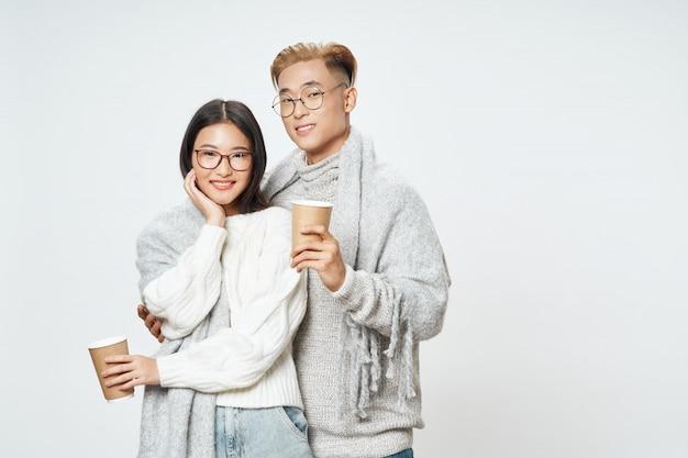 冬の服でポーズをとってアジアの女性と男性のカップル