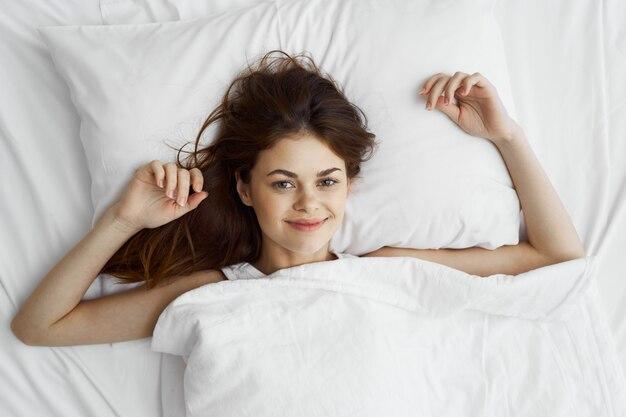 ベッドと幸せ、トップビューで美しい若い女性