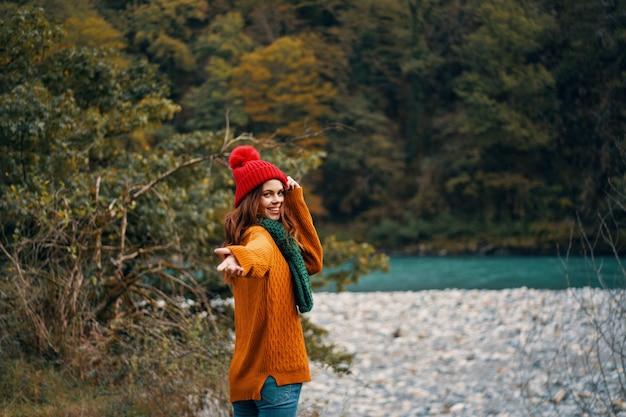 明るい服、赤い帽子、オレンジ色のセーター、緑のスカーフで森の美しい若い女性旅行、森の自然の中でハイキング