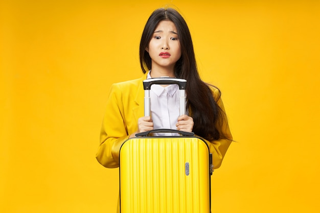 Азиатская женщина путешествует с чемоданом в руках, отдых