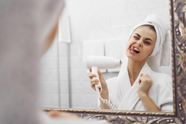 鏡の前のバスローブのバスローブの女性が彼女の顔を見る