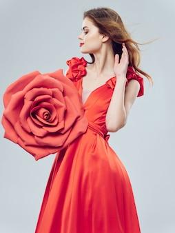 大きなバラの花と赤いドレスの若い美しい女性