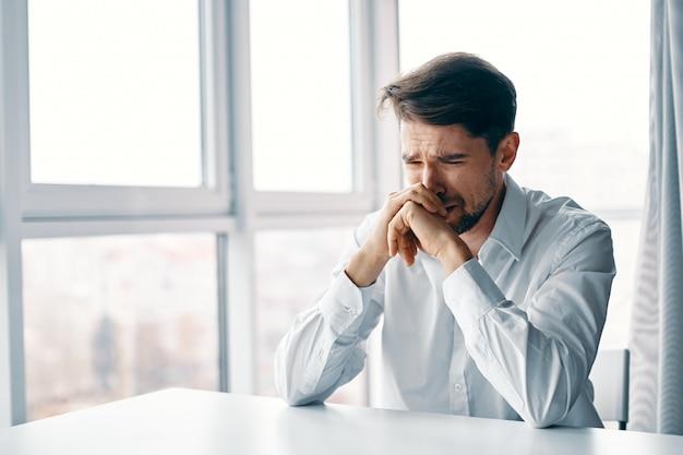 Молодой человек сидит за столом в депрессии к окну