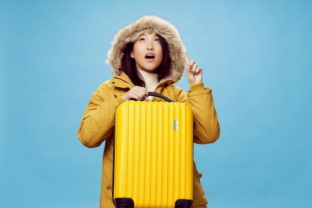 アジアの女性は彼女の手、休暇、スタジオでスーツケースと一緒に旅行します