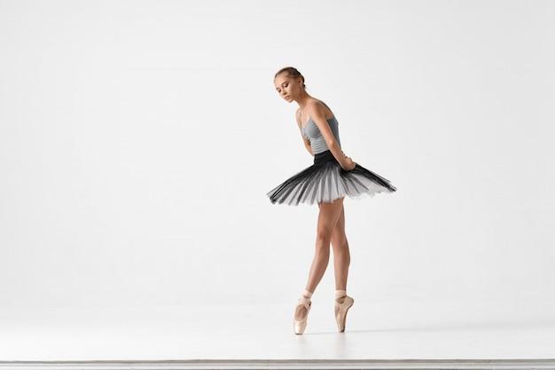 Женщина балерина танцует балет на светлой студии