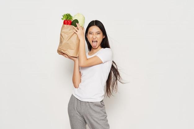 Азиатская женщина, держащая бумажный мешок, полный о здоровой пищи