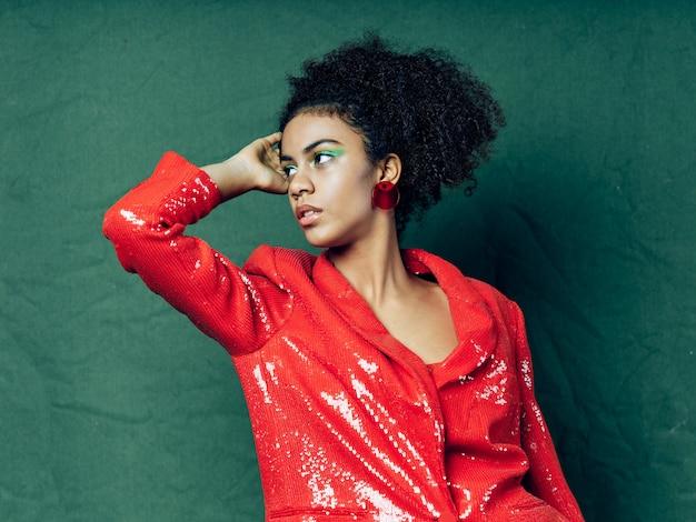 色付きの背景のポーズに光沢のあるお祭りファッション服の女性アフリカ系アメリカ人
