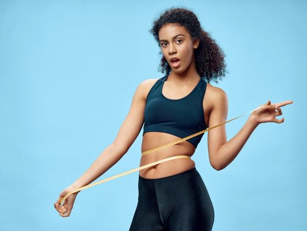 Темнокожая афроамериканка позирует в спортивном костюме и занимается спортом