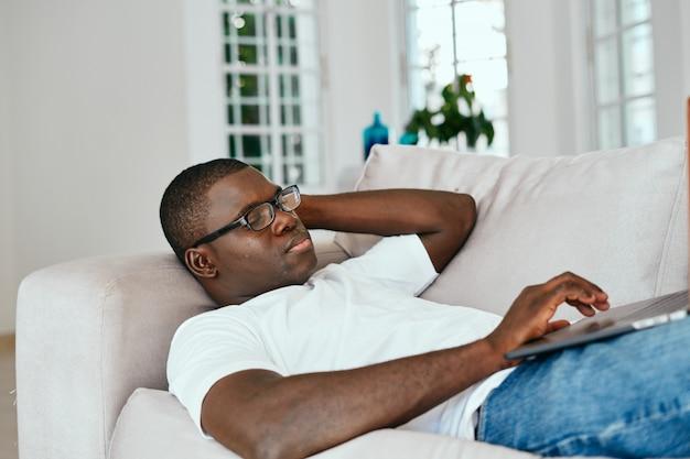 自宅でフリーランスのラップトップで働くアフリカ系アメリカ人の男