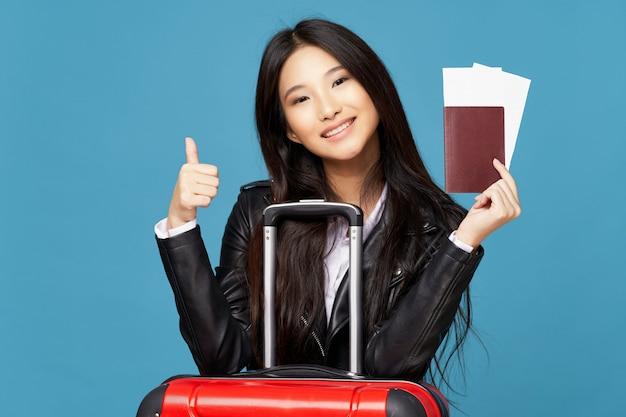 アジアの女性は、休暇中にスーツケースを持って旅行します。