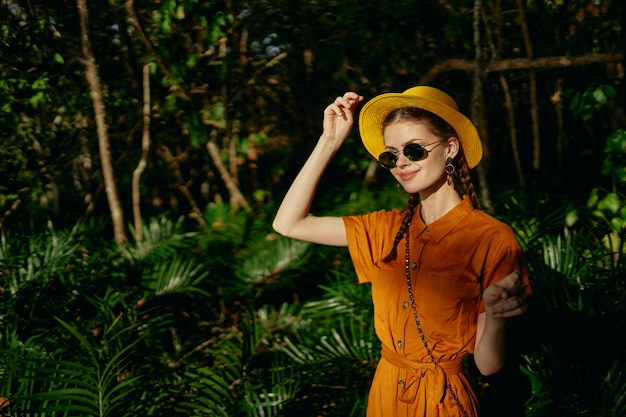 熱帯のジャングルの中で帽子を持つ若い美しい女性が公園、博物学者を歩く