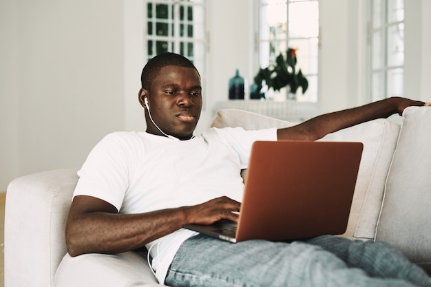 自宅でアフリカ系アメリカ人の男はラップトップで映画を見て