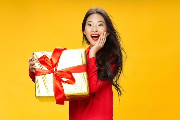 彼女の誕生日に大きな贈り物を持つアジアの女性