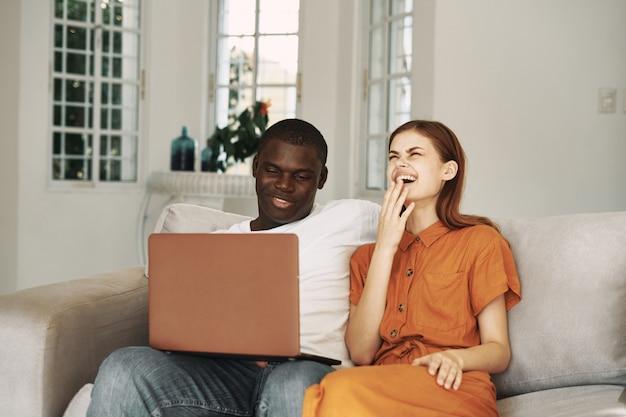 アフリカ系アメリカ人の男と白人女性のラップトップコンピューターで映画を見て
