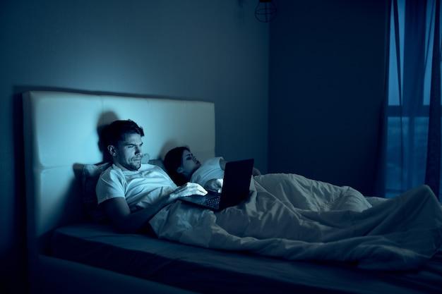 男はベッドでラップトップで働き、愛する女性は眠り、夜勤、反逆