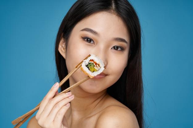 Милая молодая японская женщина ест суши