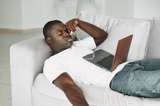 ノートパソコンで映画を見ているアフリカ系アメリカ人の男