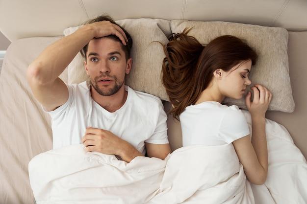 男と女はベッド、電話、不正行為、愛の関係で眠る