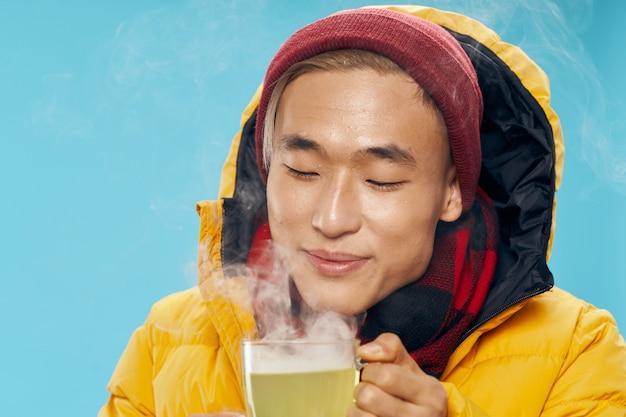 熱いお茶を飲む暖かい冬の服のアジア人