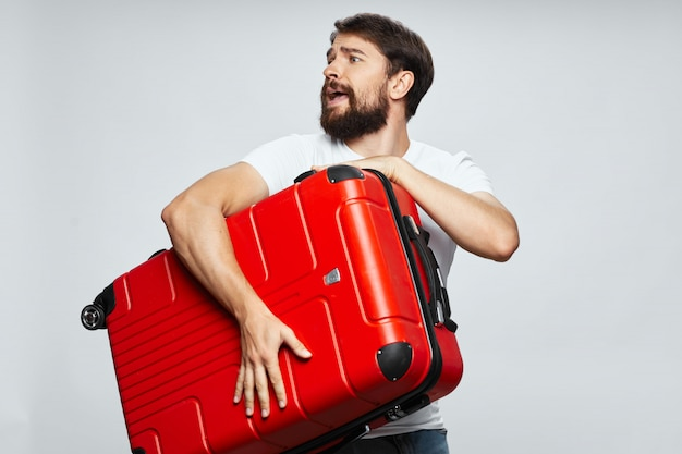 彼の手にスーツケースを持つ男性旅行者