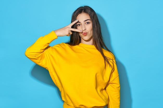 青色の背景に黄色のセーターの女性
