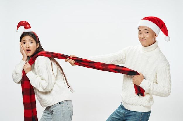 サンタの帽子を持つアジアの女性と男性のカップル