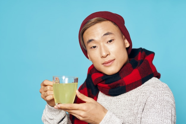 ティーカップと暖かい冬服でアジア人