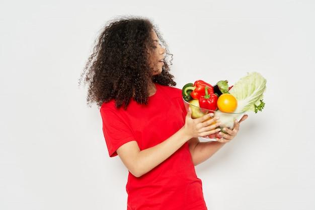 Кудрявая женщина, держащая овощную миску