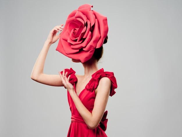 Молодая красивая женщина в красном платье с большим розовым цветком