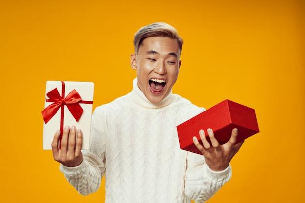 Счастливый азиатский мужчина в теплой зимней одежде открывает подарок